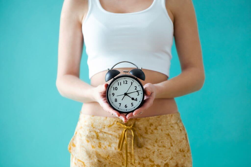 young woman holding a clock in front of her body while waiting for Beverly Hills plastic surgery