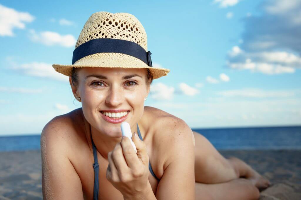 Young woman lying on beach applying sun protection to lips. How to protect your lips from the sun.