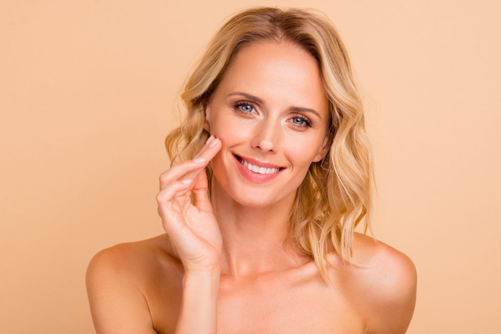 Beautiful woman touching face after facial fat grafting Beverly Hills