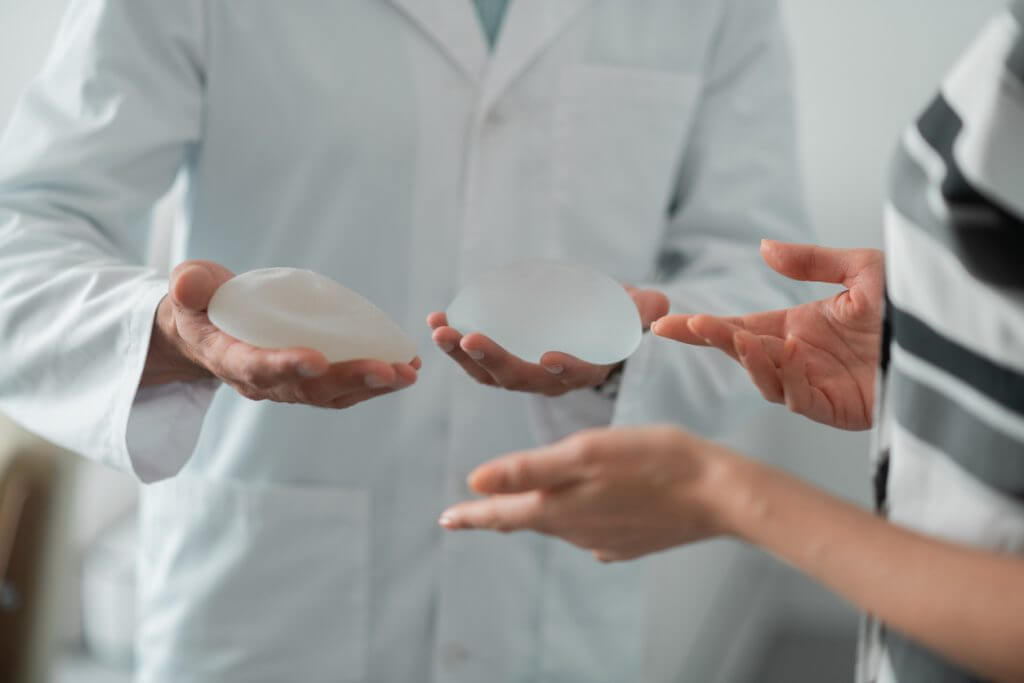 Plastic surgeon answering breast augmentation questions holding breast implants